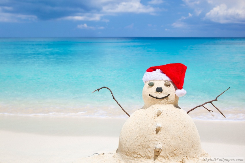 Snowman made of sand in Santa Claus hat at beach